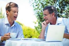 2 бизнесмена встречая в ресторане используя компьтер-книжку Стоковые Фото