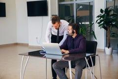 2 бизнесмена в деловой встрече обсуждая графики Стоковые Изображения