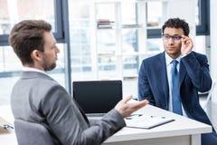 2 бизнесмена в официально носке сидя и говоря на собеседовании для приема на работу Стоковая Фотография