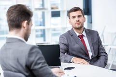 2 бизнесмена в официально носке сидя и говоря на собеседовании для приема на работу Стоковые Фотографии RF