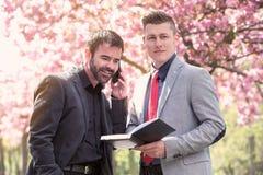 2 бизнесмена в парке с книгой и телефоном Стоковое фото RF
