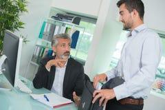 2 бизнесмена в переднем компьютере в офисе Стоковые Изображения RF