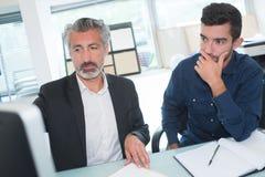 2 бизнесмена в переднем компьютере в офисе Стоковая Фотография