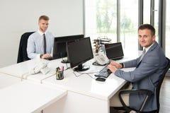 2 бизнесмена в усмехаться офиса Стоковая Фотография RF