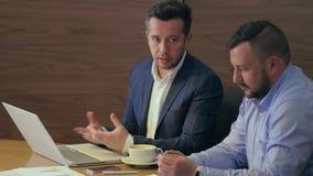 2 бизнесмена говоря в неофициальном заседании на таблице в конце офиса вверх видеоматериал