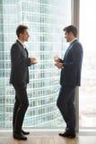2 бизнесмена говоря, имеющ перерыв на чашку кофе, стоя около вполне Стоковые Фотографии RF