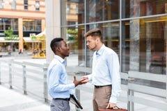 2 бизнесмена говоря и смотря документы Стоковая Фотография RF