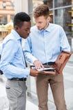 2 бизнесмена говоря и смотря документы Стоковые Изображения
