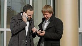 2 бизнесмена говоря на мобильном телефоне и читая сообщение Стоковые Фотографии RF