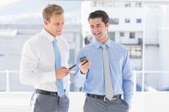 2 бизнесмена говоря друг к другу и отправляя СМС Стоковые Фото