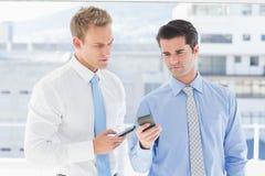 2 бизнесмена говоря друг к другу и отправляя СМС Стоковое Изображение RF