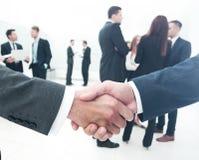 2 бизнесмена делая согласование, их коллег стоя близко Стоковые Изображения