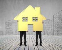 2 бизнесмена держа дом золота совместно Стоковая Фотография RF