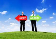2 бизнесмена держа проигравшего и победителя Стоковая Фотография RF