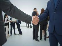 2 бизнесмена делая согласование, их коллег стоя близко Стоковое Изображение