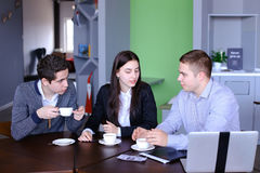 3 бизнесмена, женщина и люди обсуждая робот с чашкой te Стоковые Фото