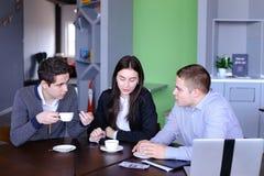 3 бизнесмена, женщина и люди обсуждая робот с чашкой te Стоковое фото RF