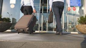 2 бизнесмена идя к авиапорту с его багажом Молодые человеки идя через автоматическую дверь современного стержня видеоматериал