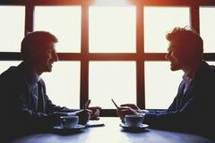 2 бизнесмена имеют обед с чашками кофе Стоковая Фотография
