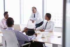 4 бизнесмена имея встречу вокруг таблицы зала заседаний правления Стоковое фото RF