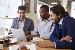 3 бизнесмена имея встречу в кофейне Стоковое Изображение