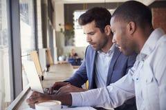 2 бизнесмена имея неофициальное заседание в кофейне Стоковые Фотографии RF