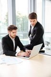2 бизнесмена используя компьтер-книжку в офисе совместно Стоковая Фотография