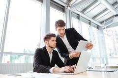 2 бизнесмена используя компьтер-книжку и таблетку в офисе совместно Стоковое Фото