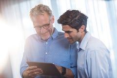 2 бизнесмена используя планшет Стоковые Изображения RF