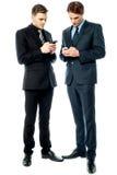 2 бизнесмена используя телефон Стоковые Фотографии RF