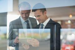 2 бизнесмена используя цифровую таблетку Стоковые Изображения RF