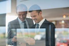 2 бизнесмена используя цифровую таблетку Стоковое Изображение