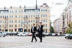 2 бизнесмена идя и говоря на сотовом телефоне в городе Стоковые Фото