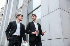 2 бизнесмена идя и говоря outdoors Стоковая Фотография RF