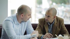 2 бизнесмена обсуждают проект над обедом 2 бизнесмена есть китайские лапши и обсуждая проект дела видеоматериал