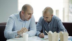 2 бизнесмена обсуждают проект над обедом 2 бизнесмена есть китайские лапши и обсуждая проект дела сток-видео