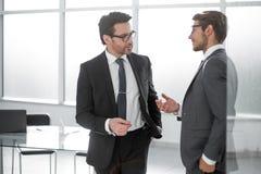 2 бизнесмена обсуждая вопросы дела стоя в офисе Стоковая Фотография RF