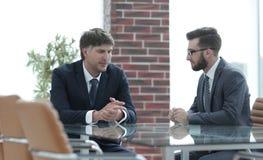 2 бизнесмена обсуждая задачи сидя на таблице офиса Стоковые Изображения