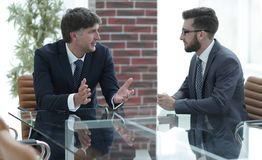 2 бизнесмена обсуждая задачи сидя на таблице офиса Стоковая Фотография