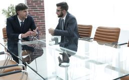 2 бизнесмена обсуждая задачи сидя на таблице офиса Стоковое Изображение