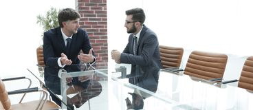 2 бизнесмена обсуждая задачи сидя на таблице офиса Стоковое фото RF