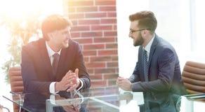 2 бизнесмена обсуждая задачи сидя на таблице офиса Стоковое Фото