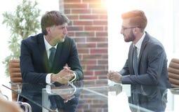 2 бизнесмена обсуждая задачи сидя на таблице офиса Стоковое Изображение RF