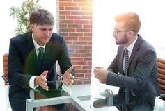 2 бизнесмена обсуждая задачи сидя на таблице офиса Стоковая Фотография RF