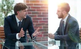2 бизнесмена обсуждая задачи сидя на таблице офиса Стоковые Изображения RF