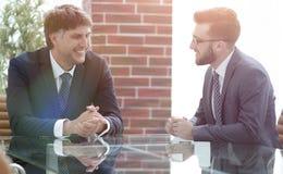 2 бизнесмена обсуждая задачи сидя на таблице офиса Стоковые Фотографии RF