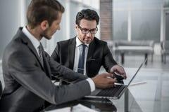 2 бизнесмена обсуждая информацию от компьтер-книжки Стоковое фото RF