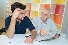 2 бизнесмена обсуждая на таблице совместно Стоковое Изображение RF