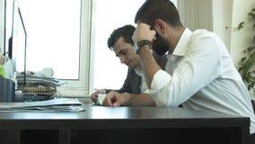 2 бизнесмена обсуждают в офисе план развития акции видеоматериалы