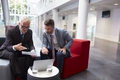 2 бизнесмена обсуждают документ в лобби современного офиса Стоковая Фотография